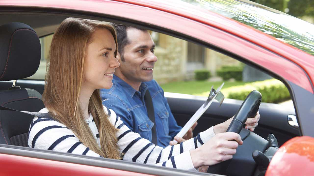 Woman having driving lesson with instructor